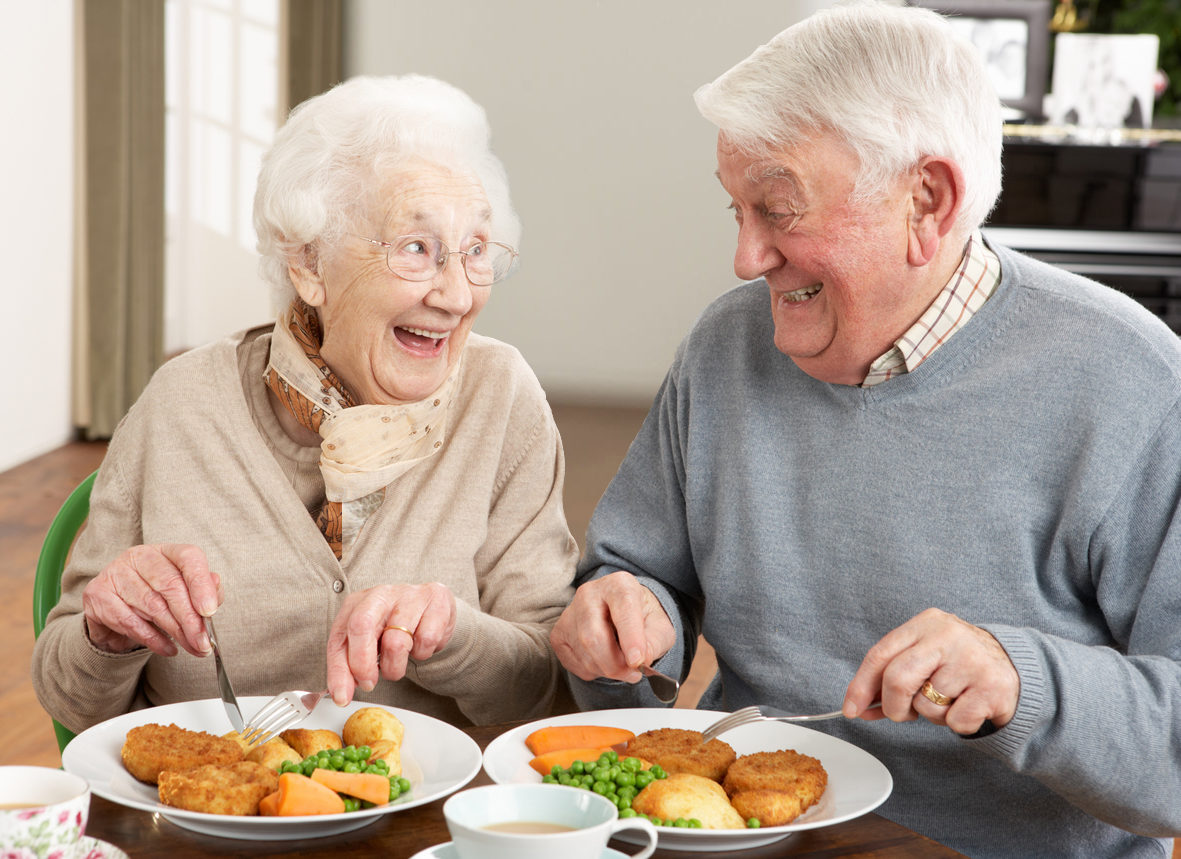 Senior Couple Enjoying Meal Together In Retirement Home