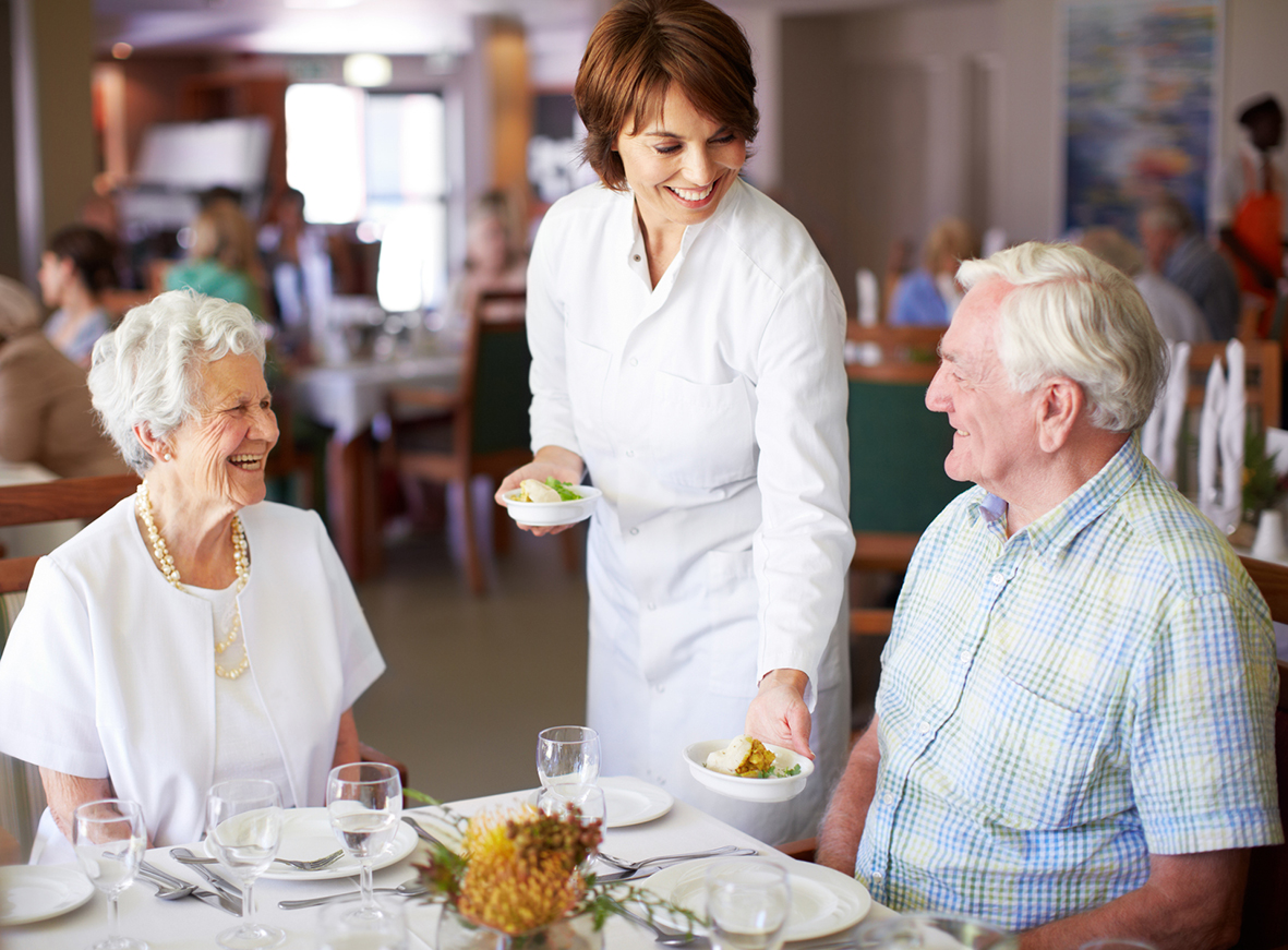 Married senior couple enjoying a lunch together while receiving friendly service